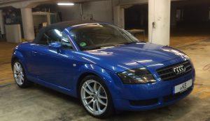 Bild zeig ein blaues Auto, dessen Dach sich öffnen lässt (Roadster)